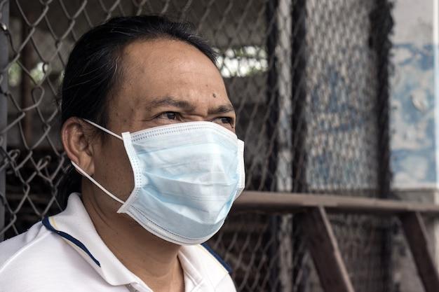 Homme asiatique portant un masque à bouche contre la pollution de l'air en usine. Photo Premium