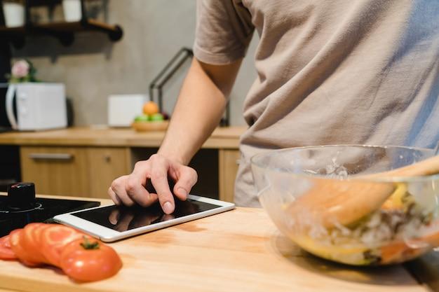 Homme asiatique à la recherche de recette sur tablette numérique et cuisson des aliments sains dans la cuisine à domicile Photo gratuit