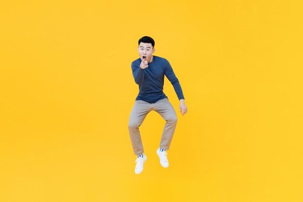 Homme Asiatique Sautant En L'air Faisant Un Geste De Pointage Photo Premium