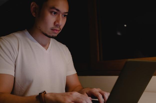 Homme Asiatique Sérieux Travaille Avec Un Ordinateur Portable La Nuit. Photo Premium