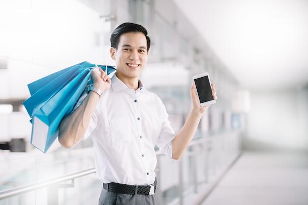 Homme asiatique sont client tenant un téléphone intelligent et un sac dans un centre commercial Photo Premium