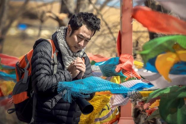 Homme Asiatique Sont La Prière Avec Des Drapeaux De Prière, Une Bannière De Bénédictions Tibétaines. Photo Premium