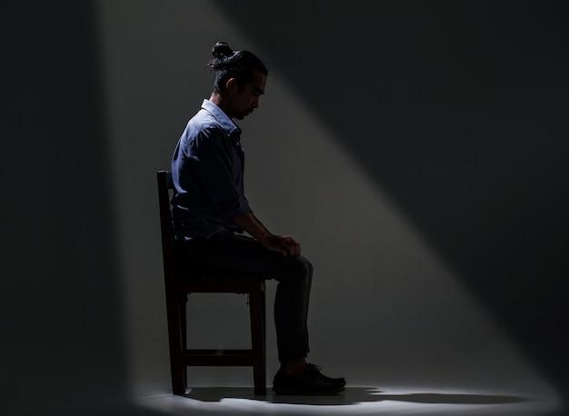Un homme asiatique souffre de dépression dans l'obscurité. Photo Premium