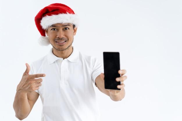 Homme asiatique souriant, bonnet de noel et pointant sur smartphone Photo gratuit