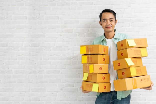 Homme asiatique tenant transporter colis brun ou des boîtes en carton sur le mur de briques Photo Premium