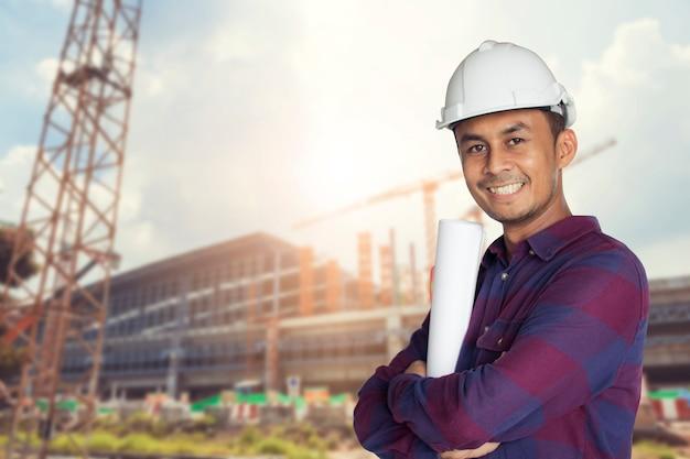 Homme asiatique thaïlandais, ingénieur portant un casque blanc et tenant bleu impression debout avec grand sm Photo Premium