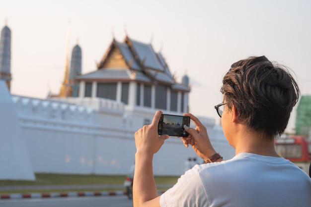 Homme asiatique voyageur utilisant un téléphone portable pour prendre une photo tout en passant des vacances à bangkok, thaïlande Photo gratuit