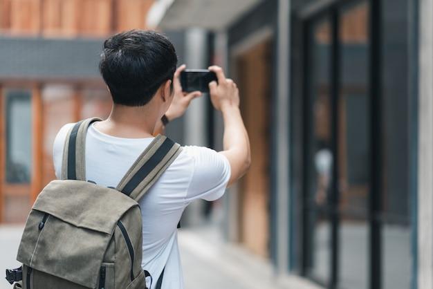 Homme asiatique voyageur utilisant un téléphone portable pour prendre une photo tout en passant des vacances à pékin, chine Photo gratuit