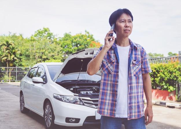 Homme d'asie se tenant devant une voiture cassée appelant à l'aide Photo Premium