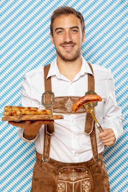 Homme avec assiette en bois de saucisses allemandes Photo gratuit