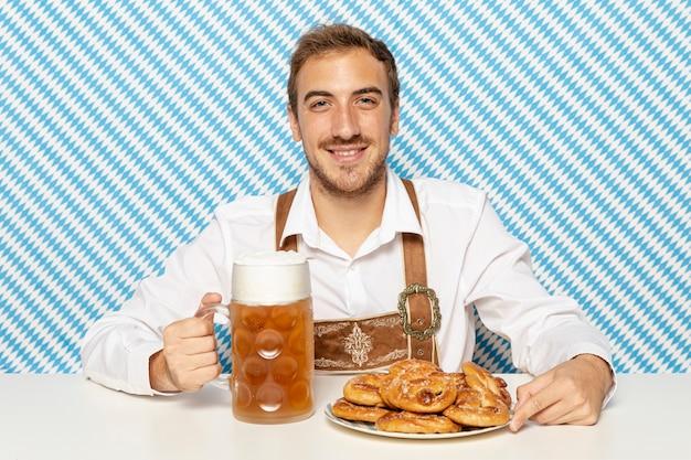 Homme avec assiette de bretzels et de bière Photo gratuit
