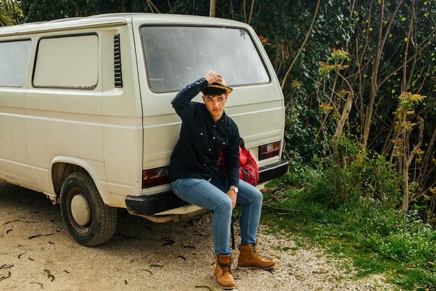 Homme Assis à L'arrière De La Camionnette Touchant Son Chapeau Sur La Tête Photo gratuit