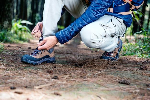 Homme assis et attachant son lacet de trekking Photo Premium