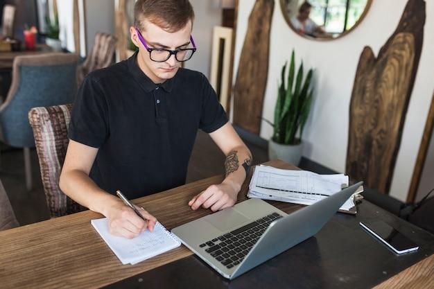 Homme assis avec bloc-notes et ordinateur portable à la table Photo gratuit