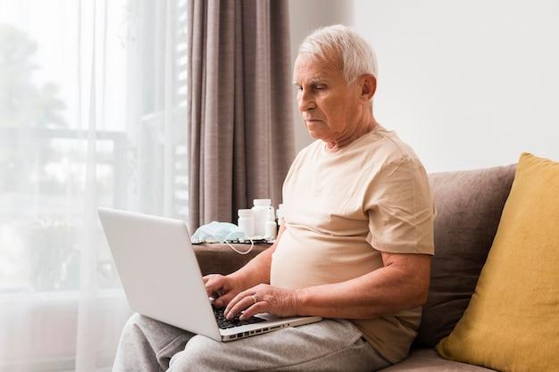 Homme Assis Sur Un Canapé Avec Ordinateur Portable Photo gratuit