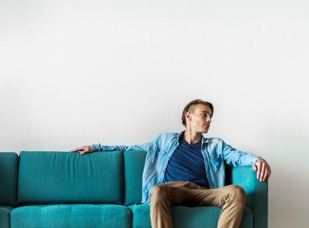 Homme assis sur un canapé Photo gratuit
