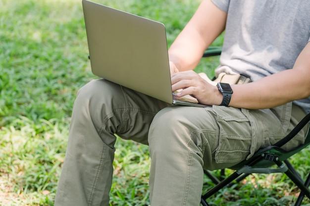 Homme assis sur une chaise de camping et travaillant avec un ordinateur portable dans le jardin Photo Premium