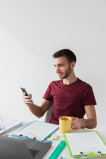 Homme assis sur une chaise et regardant son téléphone Photo gratuit