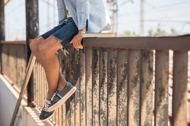 Homme assis sur une clôture en attente de train Photo gratuit