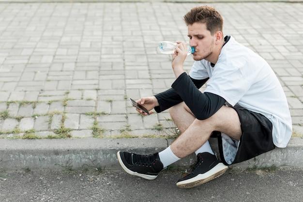 Homme assis sur le côté, hydratant Photo gratuit