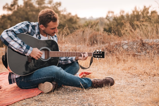 Homme assis sur une couverture, jouer de la guitare Photo gratuit