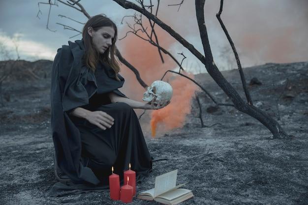 Homme assis avec un crâne dans la main et en regardant Photo gratuit