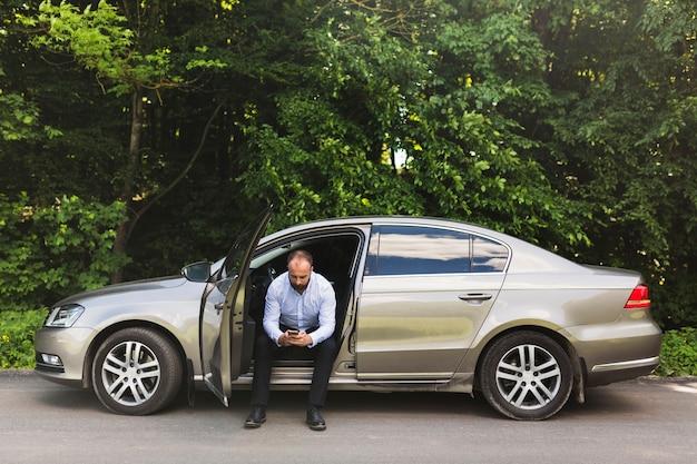 Homme assis dans une voiture avec porte ouverte à l'aide d'un téléphone mobile Photo gratuit