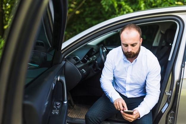 Homme assis dans une voiture avec la porte ouverte en regardant l'écran du téléphone portable Photo gratuit