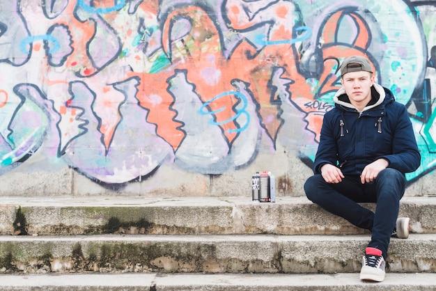 Homme Assis Devant Le Mur De Graffitis Photo gratuit