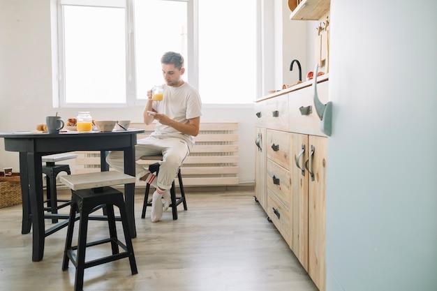 Homme assis devant une table à manger ayant du jus avec un téléphone portable Photo gratuit