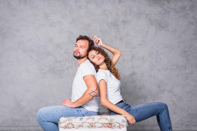 Homme assis dos à dos de femme Photo gratuit