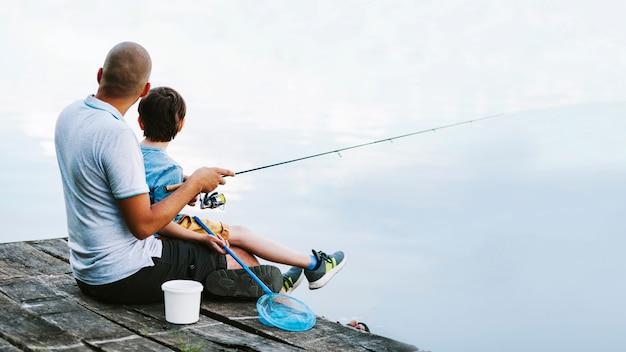 Homme assis sur la jetée avec son fils pêchant sur le lac Photo gratuit