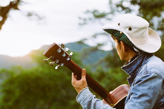 Un Homme Assis Joyeusement à Jouer De La Guitare Dans La Forêt Seul. Photo gratuit