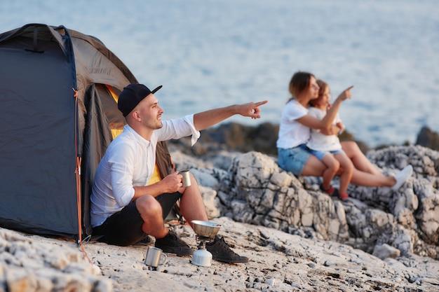 Homme Assis Sur La Plage Rocheuse En Regardant Le Coucher Du Soleil, Femme Et Fille Assise à Proximité. Photo Premium
