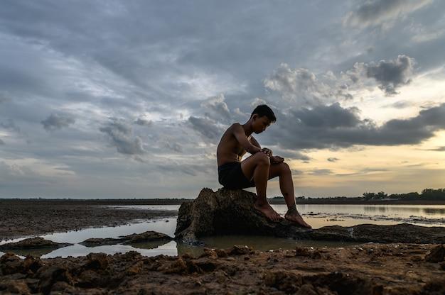 Un homme assis pliait ses genoux à la base de l'arbre où le sol était sec et les mains placées sur la tête. Photo gratuit