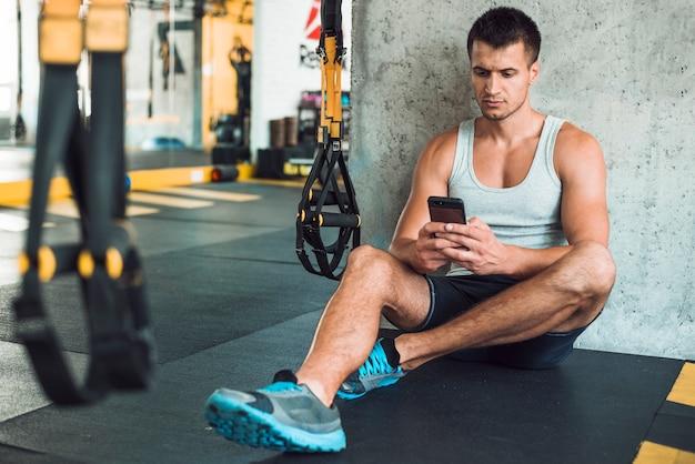 Homme assis sur le sol à l'aide de téléphone portable dans la salle de sport Photo gratuit