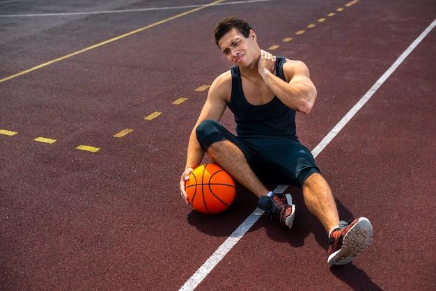 Homme assis sur le terrain de basket Photo gratuit