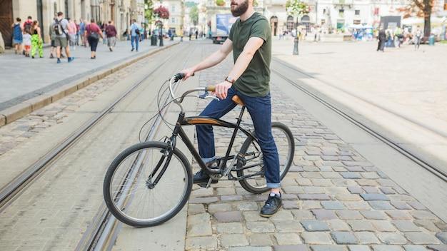 Homme assis à vélo dans la ville Photo gratuit