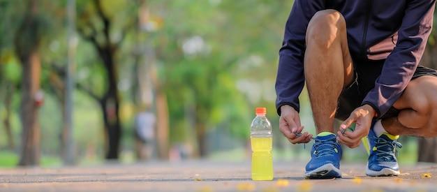 Homme athlète attachant des chaussures de course dans le parc en plein air Photo Premium