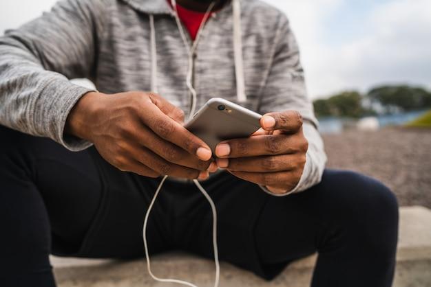 Homme Athlétique à L'aide De Son Téléphone Portable. Photo Premium