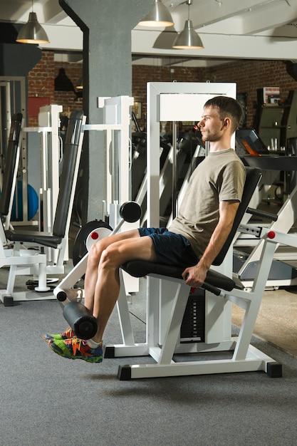 Homme athlétique balancer les muscles abdominaux dans une salle de sport Photo Premium