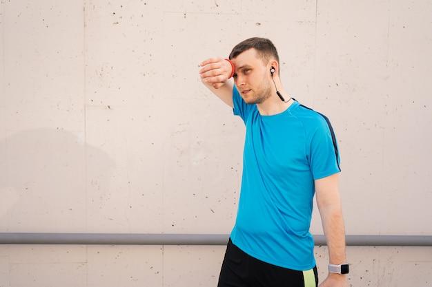 Homme Athlétique Fatigué Essuyant La Sueur Sur Son Front Photo gratuit