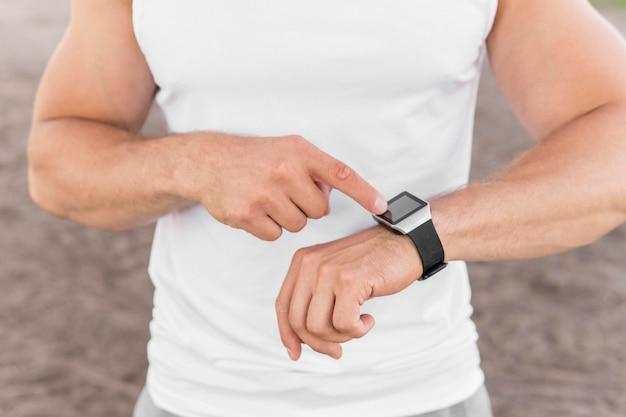 Homme Athlétique Montrant Sa Smartwatch Photo gratuit