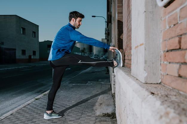 Homme Athlétique S'échauffant Sur La Rue Photo gratuit