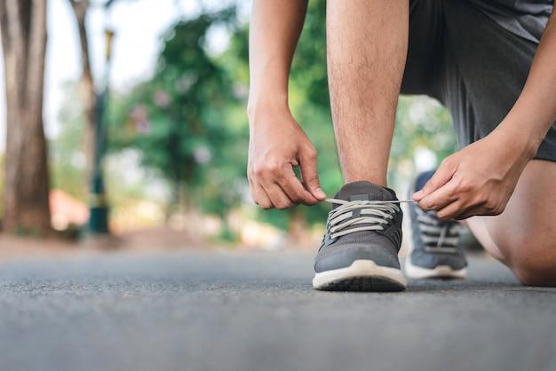 Homme attachant des chaussures de course sur le parc Photo Premium