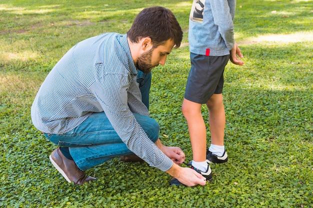 Un homme attache le lacet de son fils dans le parc Photo gratuit