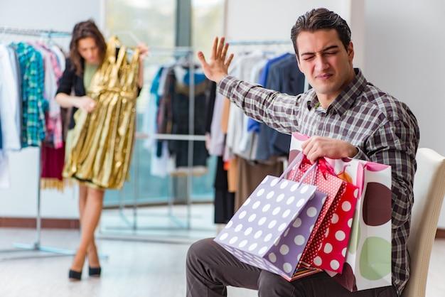 Homme Attendant Sa Femme Pendant Les Achats De Noël Photo Premium