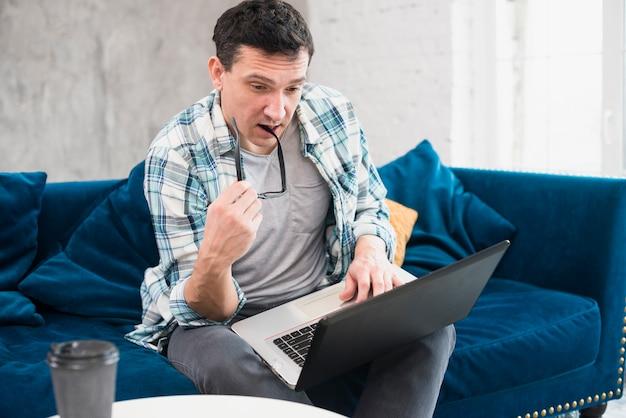 Homme attentif regardant un ordinateur portable à la maison Photo gratuit