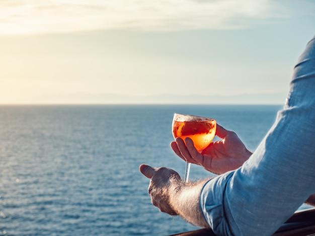 Homme attrayant et élégant à lunettes de soleil, tenant un verre de beau cocktail rose Photo Premium