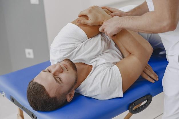 Homme Au Cabinet Médical. Le Physiothérapeute Est En Cours De Rééducation. Photo gratuit